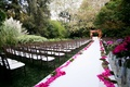 Hotel Bel-Air Swan Lake wedding ceremony with white aisle runner and bright pink flower petals
