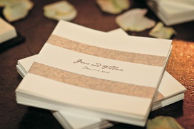 Off-white cocktail napkin with bride and groom's names, wedding date, and decorative tan bands
