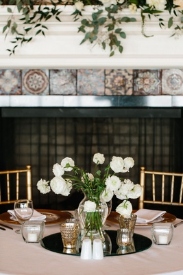 Mirror disk on wedding reception table with vase filled with white flowers at reception