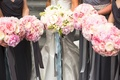 bride and bridesmaids in gray dresses with pink and white greenery bouquets and fabric streamers