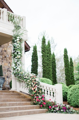 2400 on the river wedding, garland of flowers and greenery trails from balcony down bannister