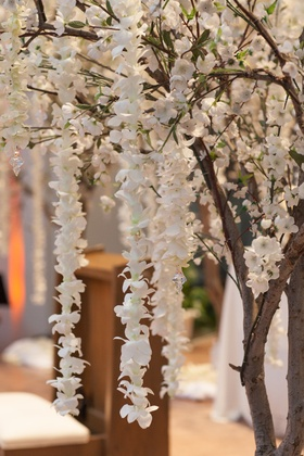 Wedding ceremony with cherry blossom tree decorations and garlands of white orchids