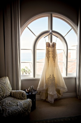 Ines Di Santo wedding dress hanging in window of Casa Del Mar bridal suite lace strapless appliques