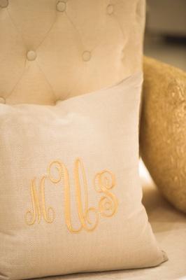 Wedding reception with throw pillow with gold monogram on elegant sofa