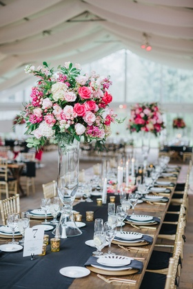 wedding reception centerpiece with greenery, pink roses, white flowers, clear stand