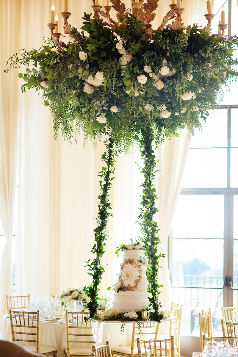 wedding cake on suspended table from floral chandelier