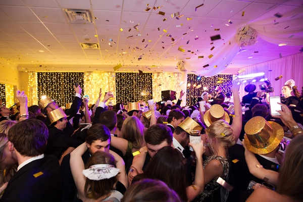 Wedding guests on dance floor in new year's eve tiaras and party hats with gold confetti in air
