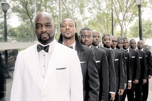 Groom in white tuxedo and groomsmen in black tuxes