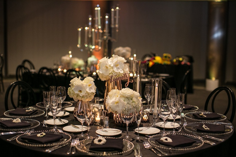 Three small floral arrangements as centerpiece on wedding reception table with black linens