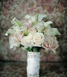 White and pink roses and calla lilies bouquet wrapped with white fabric