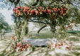 outdoor wedding ceremony austin texas greenery pink orange coral flowers at base and arch