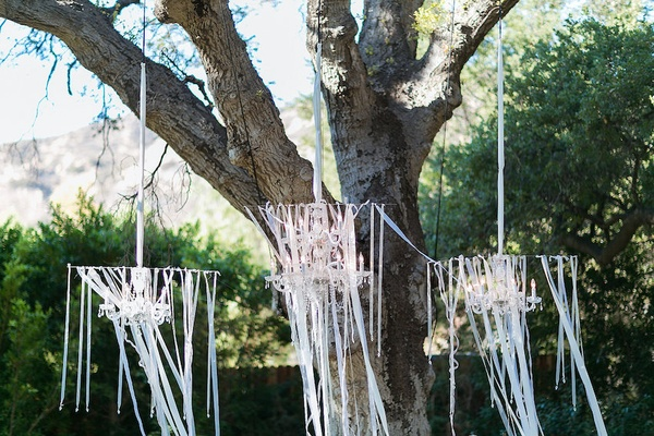 Outdoor wedding ceremony with crystal chandeliers and white ribbons hung from a tree at altar