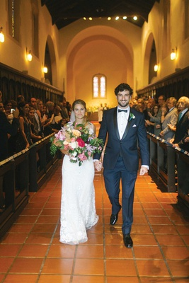 Bride with large tropical bouquet and groom in tuxedo walking down aisle church terracotta tiles