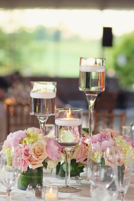 Floating candles in monet glass vases and short arrangements