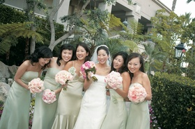 Jenny Yoo and bridesmaids in strapless pastel green dresses carrying light pink bouquets