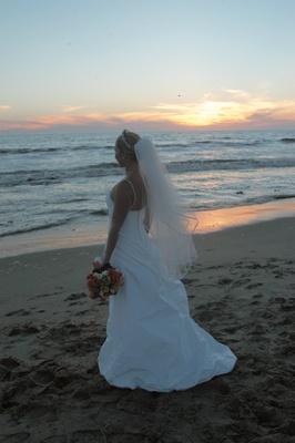 bride wearing wedding dress looks at ocean
