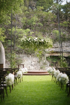 Outdoor wedding ceremony with white flowers suspended over the altar