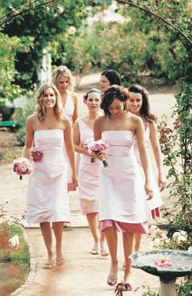 Bridesmaids in pink dresses walk through rose garden