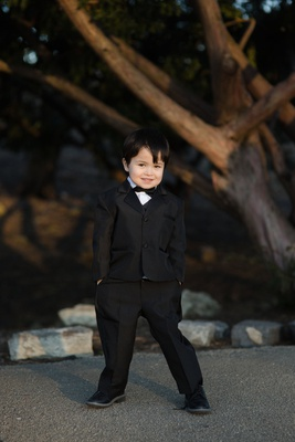 adorable ring bearer in black tuxedo with his hands in his pockets