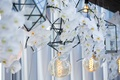 a unique display for hanging light bulbs geometric lanterns and cascading white orchids