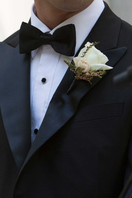 groom tuxedo and bow tie with white rose and small pink rose bud boutonniere