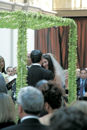 Bride and groom under chuppah of green dendrobium orchids