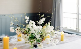 small flower arrangement with white japaense ranunculuses and corylopsis extending