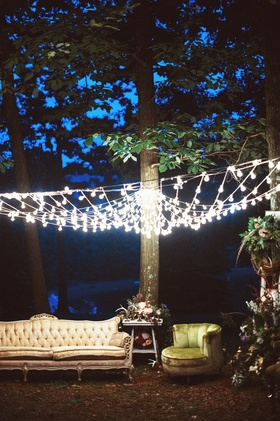 Outdoor wedding reception lounge area with vintage seating under a canopy of light bulbs