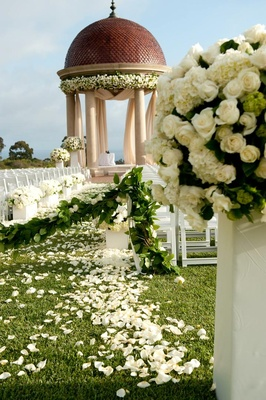 Floral arrangements on pedestals leading to chuppah