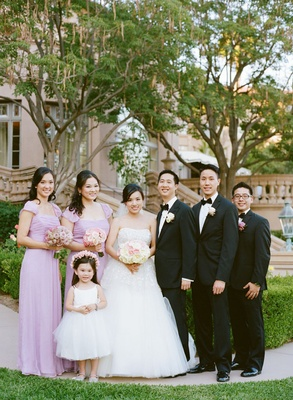 bridal party of newlyweds, flower girl, two groomsmen and two bridesmaids in purple