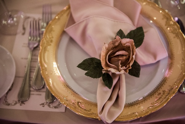 gold-rimmed charger, blush napkin, fabric rose napkin ring