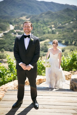 """bride in reem acra wedding dress with beaded cap sleeves approaches groom for """"first look"""""""
