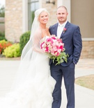 bride in strapless wedding dress with veil and large pink rose bouquet groom in navy suit brown shoe