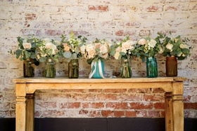 bridal party wedding bouquets in mason jars on wood console table in front of brick wall pink white