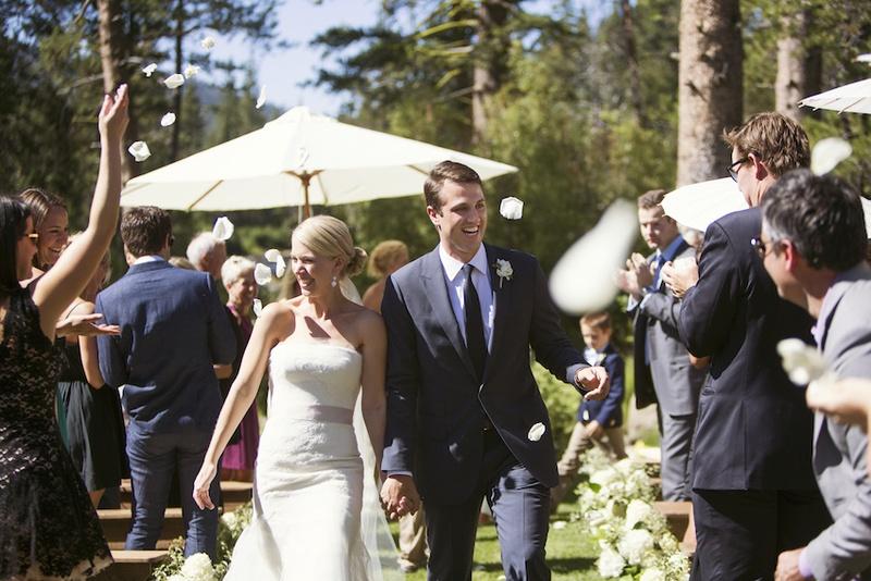 Wedding guests throwing petals on bride and groom