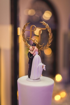 Wedding cake topper with bride popping foot and kissing groom monogram in gold cake topper