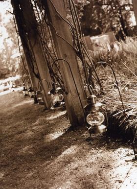 Sepia tone image of ceremony aisle lanterns on shepherd hooks