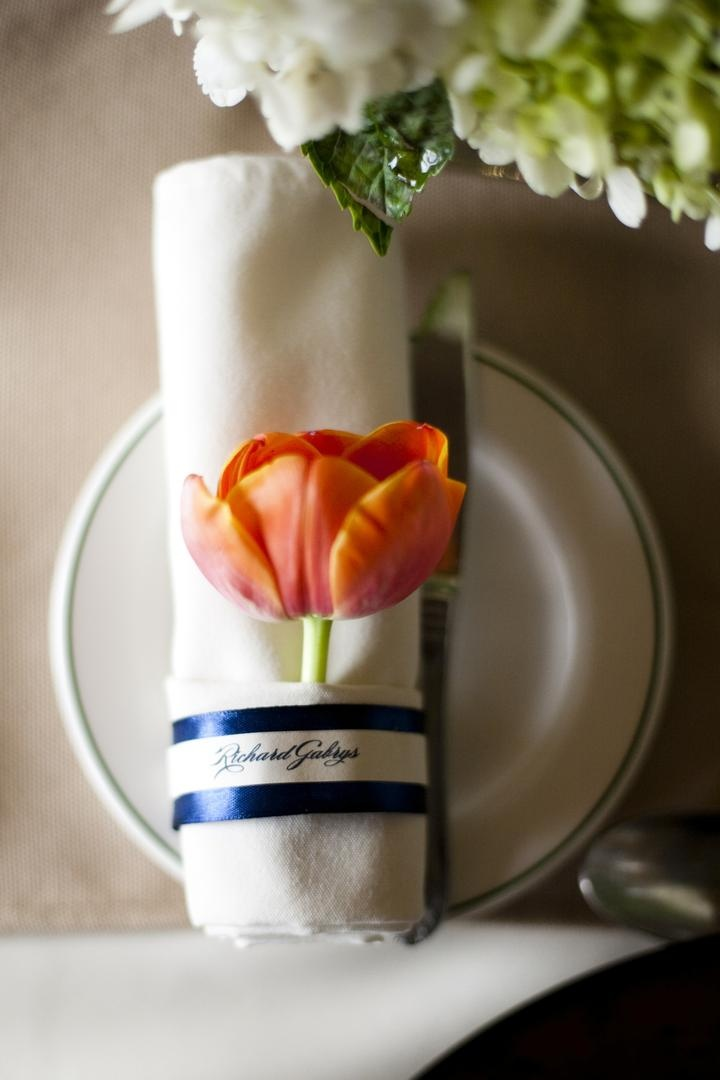 Rolled napkins wrapped in blue ribbon and tulip