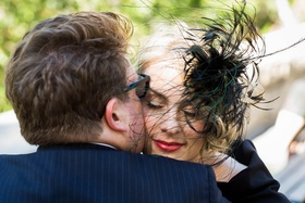 Groom in blue pinstripe suit kisses blonde bride in black dress, feather headpiece, red lipstick