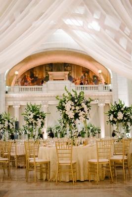 wedding reception columns gold chairs ivory linen greenery white flower centerpiece heatherlily