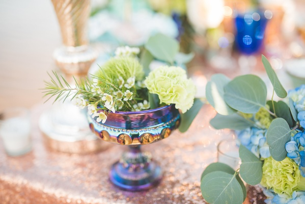 colorful, iridescent goblet with greenery on rose gold sequin table linen