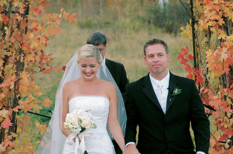 Newlyweds recessional with fall leaves in background