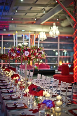 tall centerpieces with red and pink flowers, fake candles, king's table long reception table