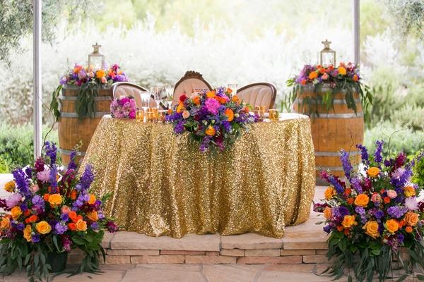 colorful wedding reception décor berry tone floral arrangements gold sequin table linens desert