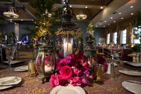 lantern and rose centerpieces, gold table number indoor forest theme wedding reception