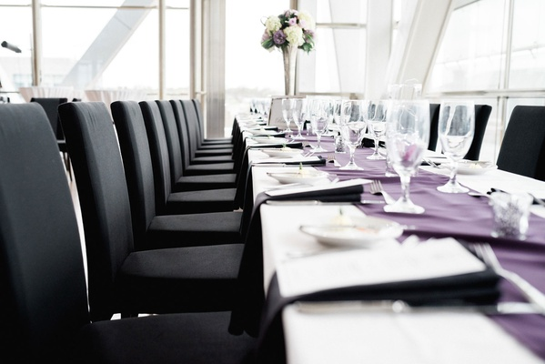 Wedding reception light bright venue with long table purple linen black chairs high centerpiece