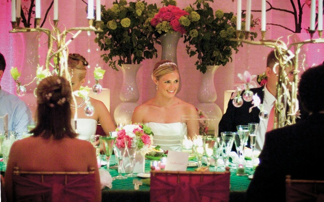 bride sits at table decorated with green linens and candelabras made of branches