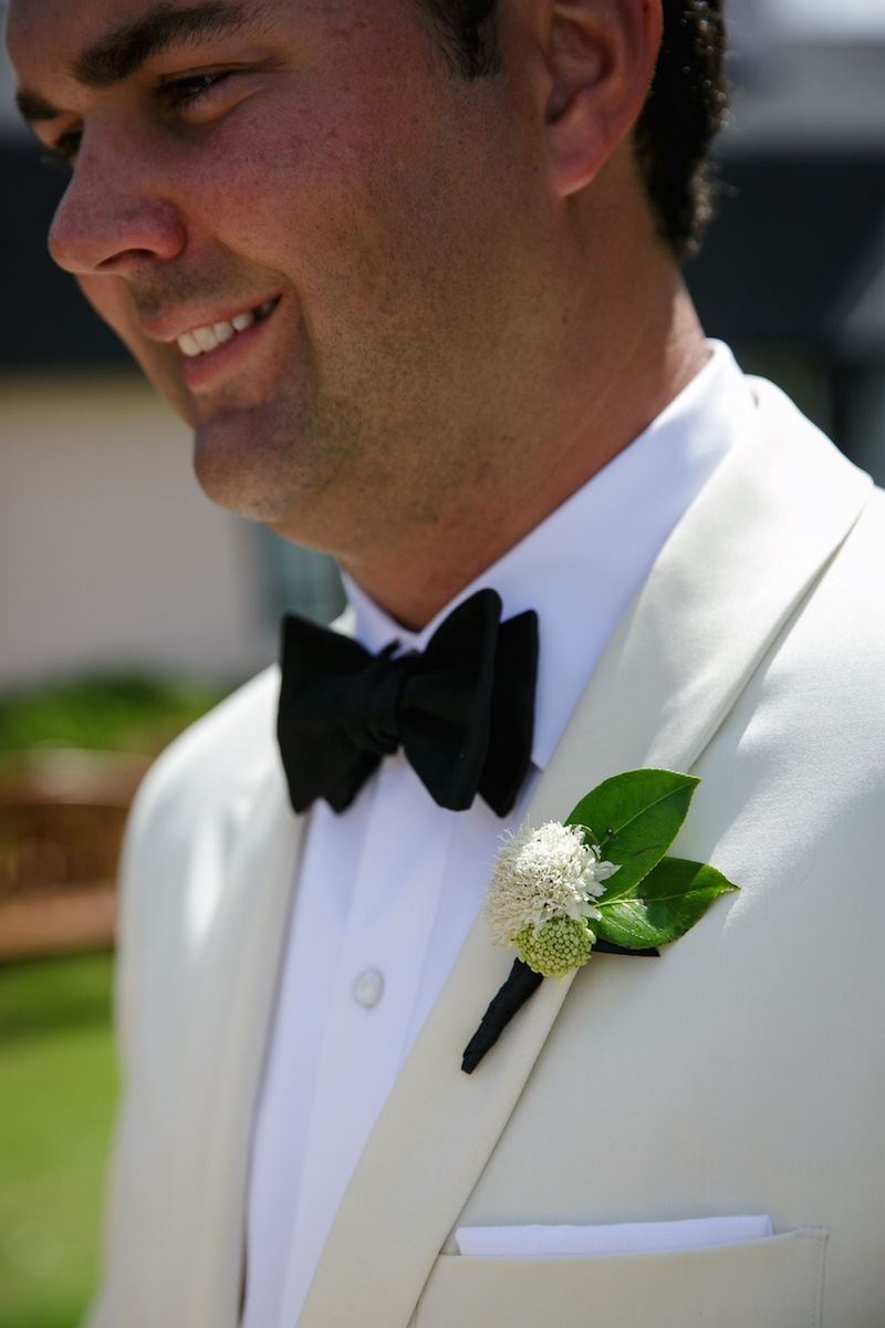 Groom in ivory tuxedo jacket with white and green leaf boutonniere