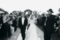 Black and white photo of couple walking up the aisle