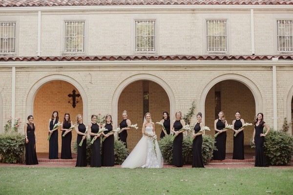 bridesmaids in black dresses from aqua carrying presentation bouquet of calla liles